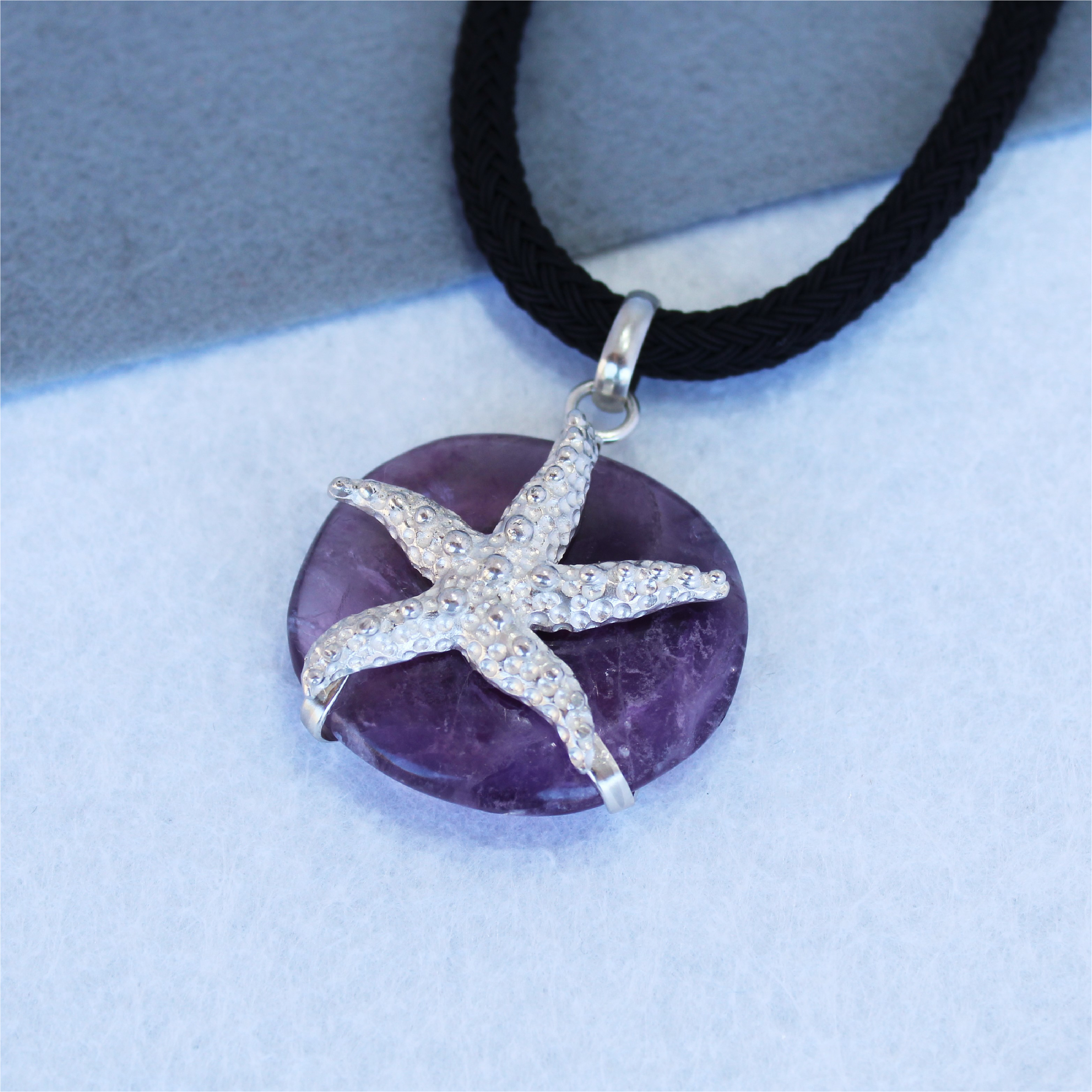 Colgante en plata de ley 925 con estrella de mar y amatista. Diseño exclusivo de Quela