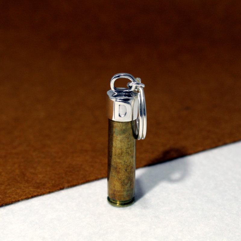 LLavero personalizad montado en plata de ley 925 con inicial y vaina de bala. Exclusivo de Quela. Joyas hechas a mano